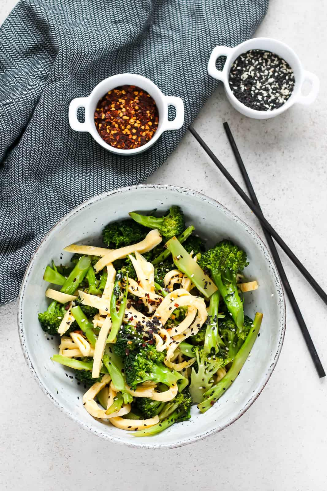 overhead photo of pan-fried broccoli tossed with egg ribbons and sprinkled with black and white sesame seeds in a blue bowl
