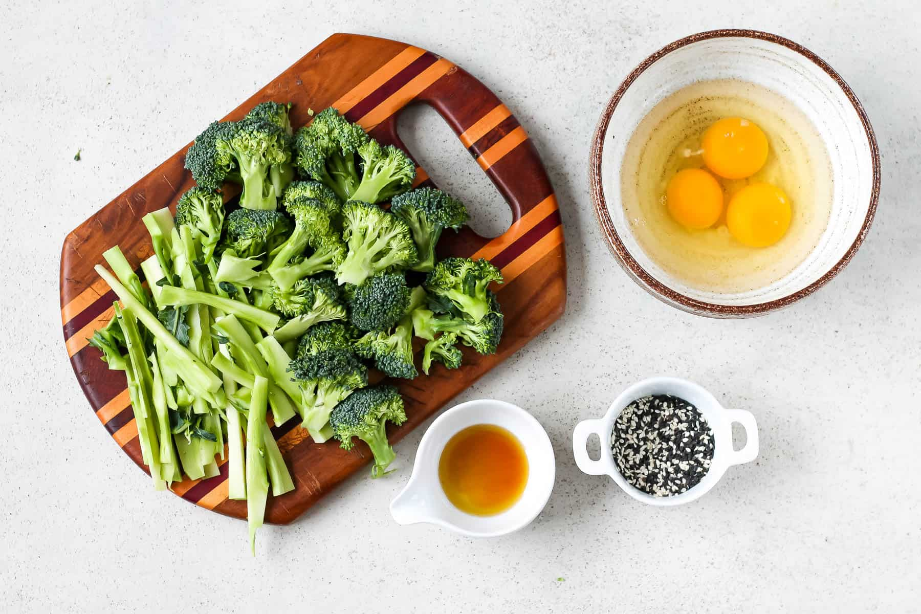 broccoli, eggs, sesame oil, and sesame seeds on a grey background