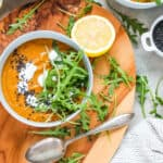 overhead photo of vegan carrot ginger soup in a blue bowl scattered with arugula leaves