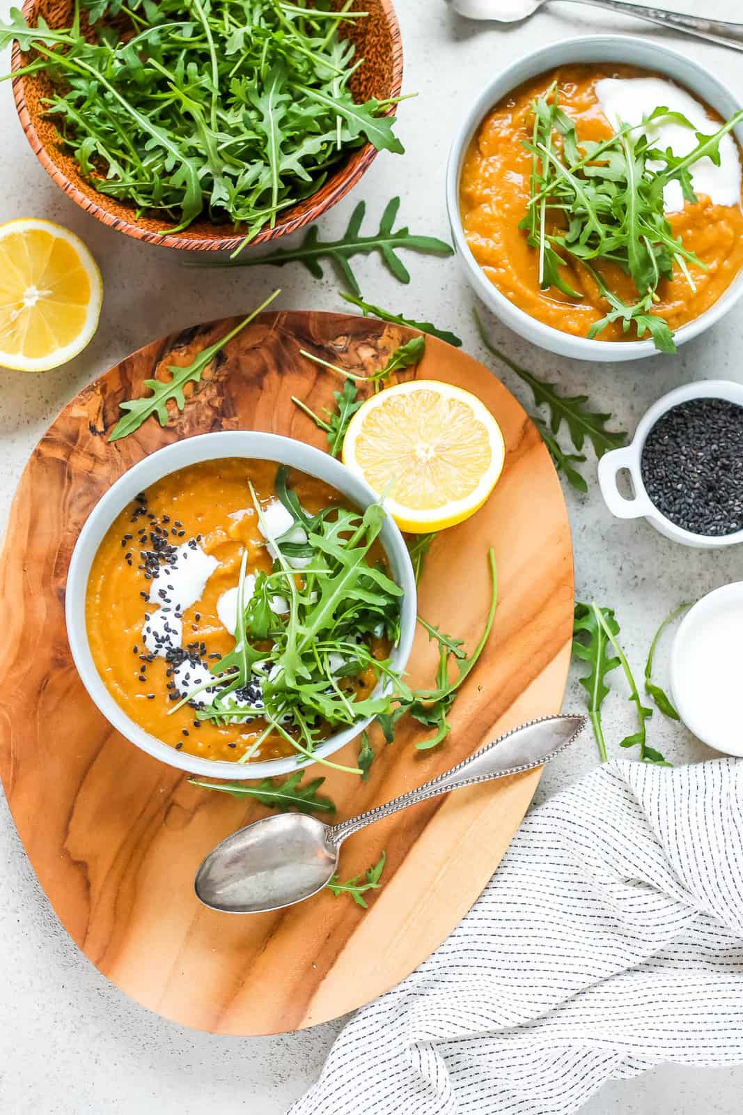 overhead photo with two bowls of vegan carrot ginger soup on a grey background