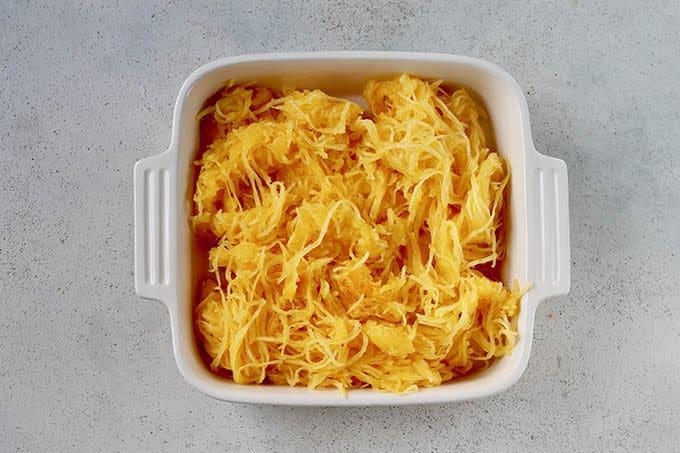 spaghetti squash noodles in a white casserole dish