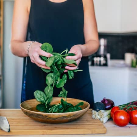 spinach leaves being tossed in a wooden bowl