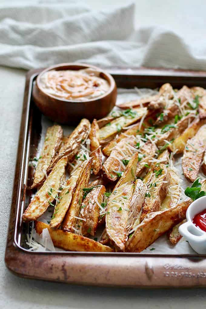 crispy potato wedges on a sheet pan scattered with parmesan and herbs