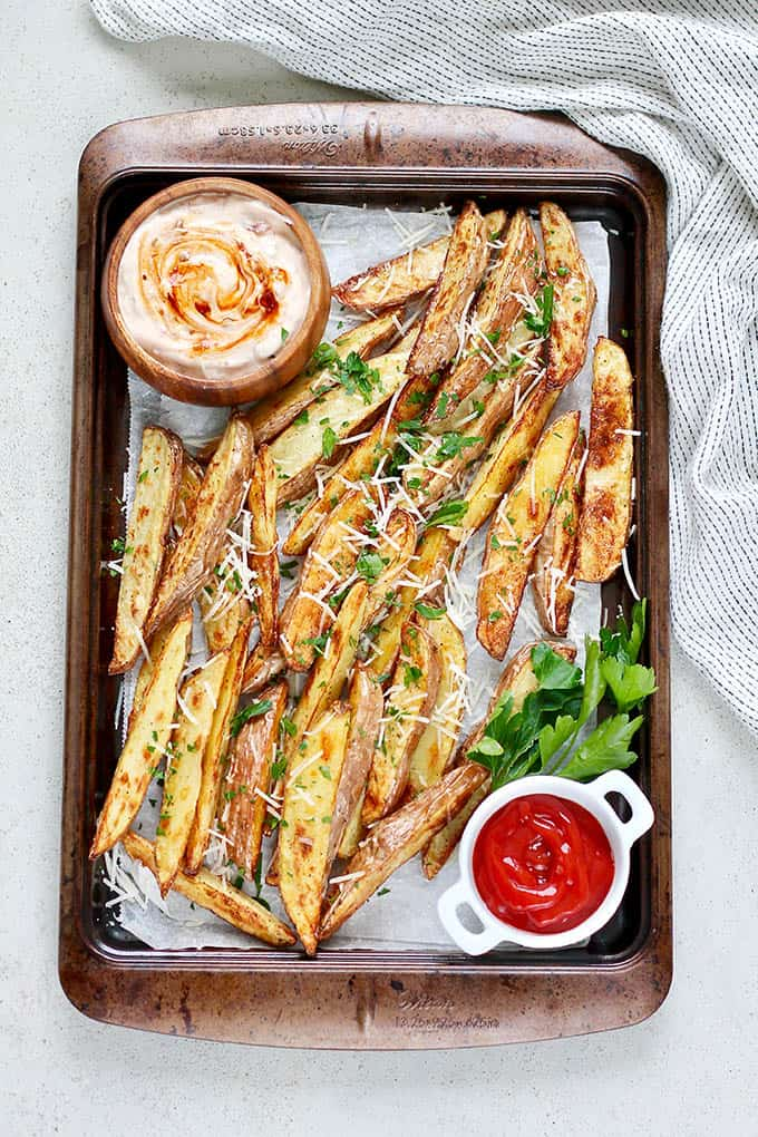 crispy potato wedges on a metal tray with ketchup and chipotle sauce