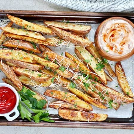 crispy baked potato wedges with chipotle dipping sauce on a metal tray