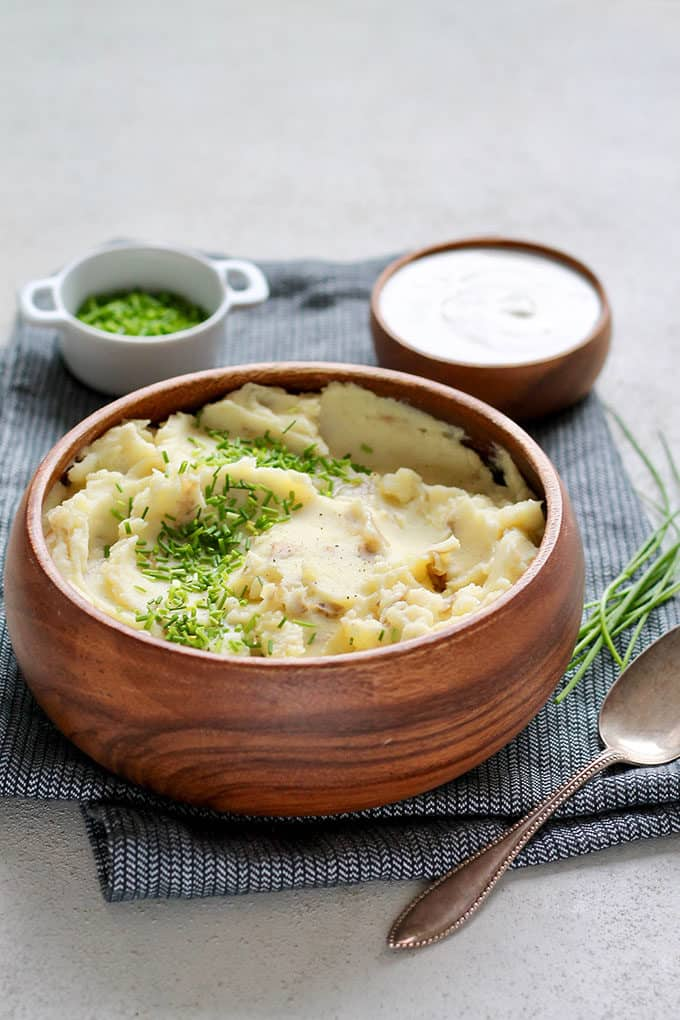 greek yogurt mashed potatoes in a wooden bowl topped with chives