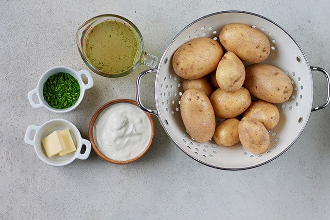 potatoes in a white colander with vegetable broth, greek yogurt, chives, and butter to the side
