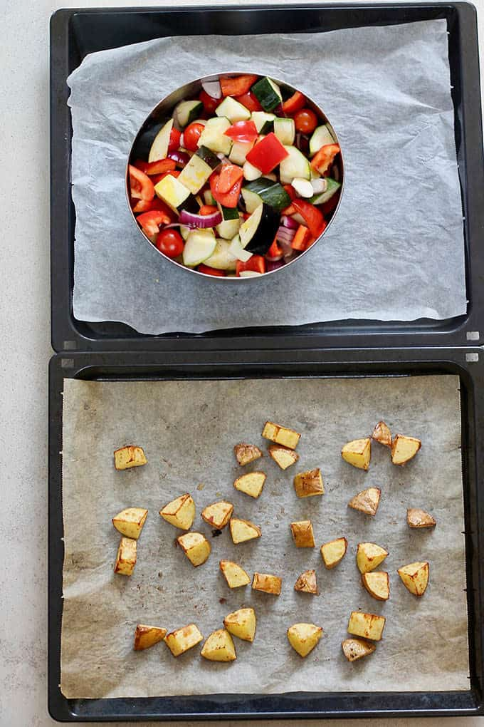 a tray of roasted potatoes and a bowl of vegetables
