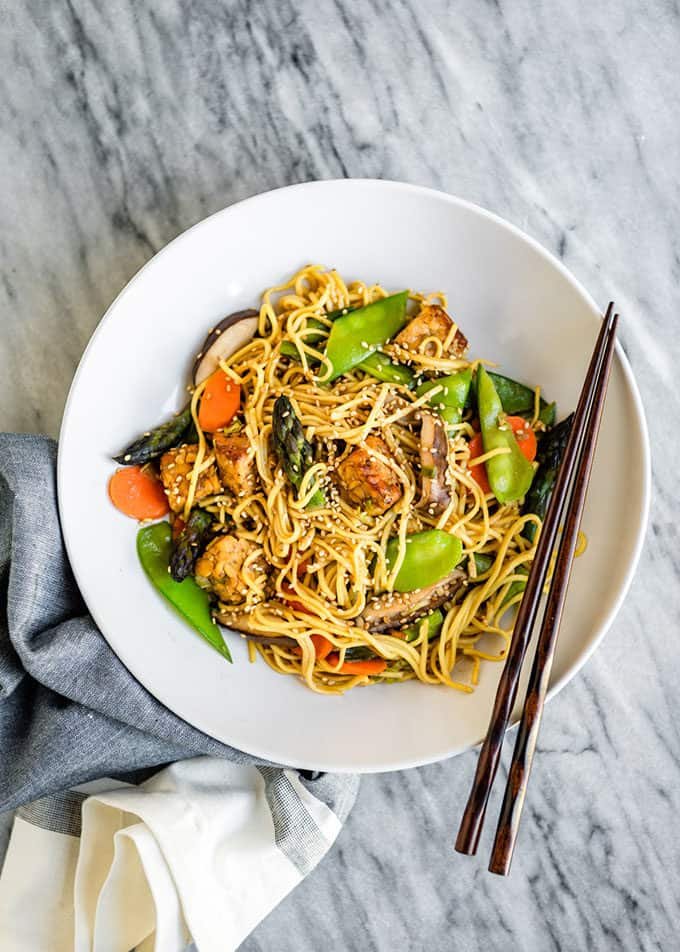 spring vegetable lo mein in a white bowl with black chopsticks