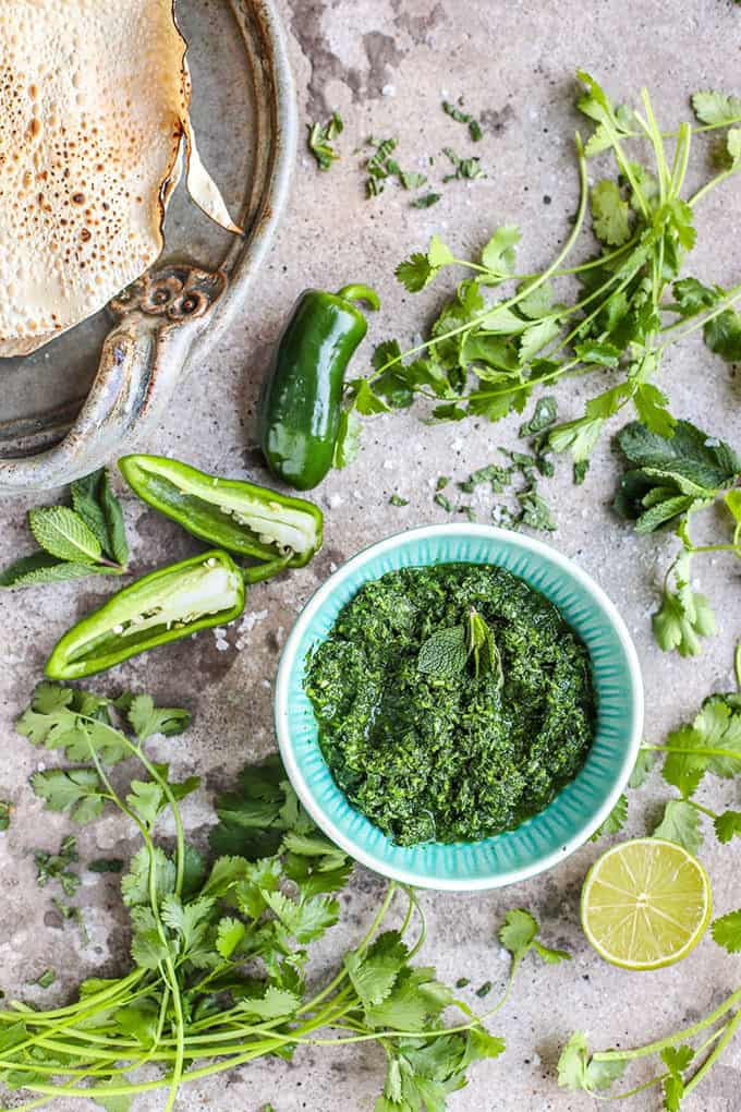 coriander mint chutney on a concrete background with jalapenos, lime, and coriander leaves scattered about