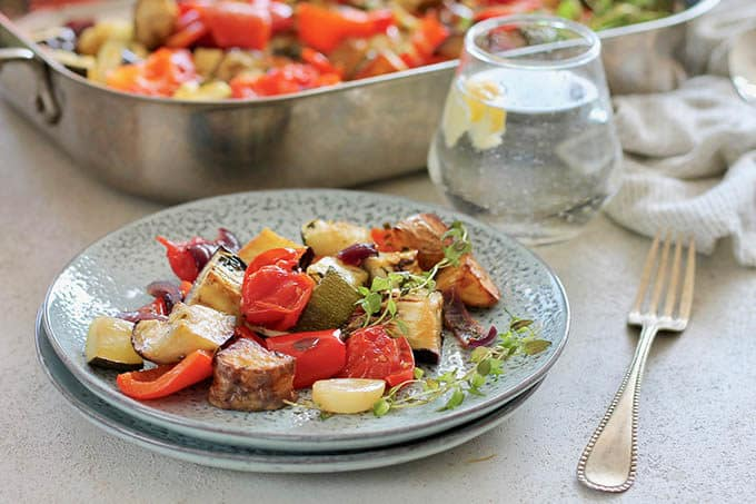 mediterranean roast vegetables on a blue plate on a grey background