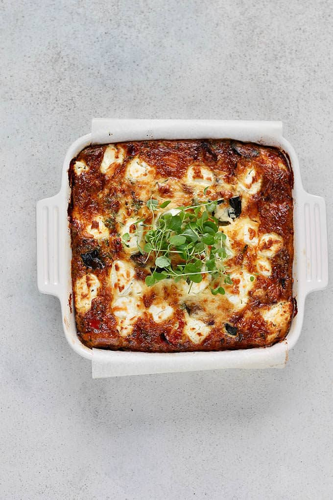 baked frittata in a white casserole dish topped with fresh herbs