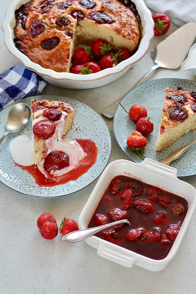 roasted strawberries in a white casserole dish with two blue plates with strawberry cake in the background