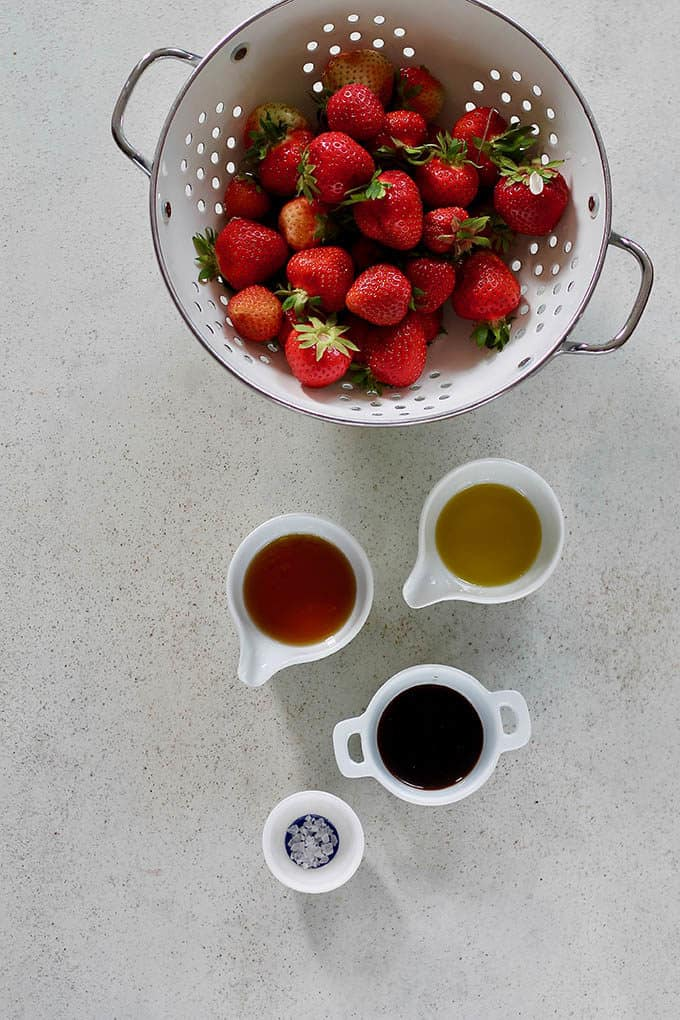 fresh strawberries in a white colander with small white pots of olive oil, balsamic, maple syrup, and salt to the side