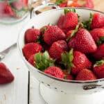 strawberries in a white colander
