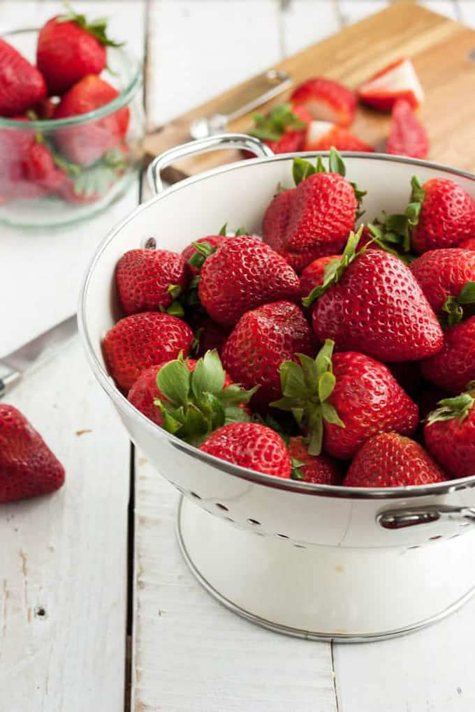 strawberries in a white colander