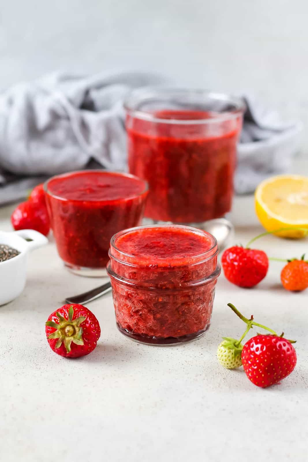 three jars of strawberry chia jam on a grey background with strawberries scattered around