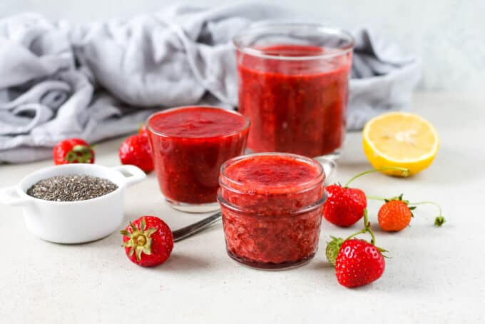 three jars of strawberry chia jam on a grey background with some strawberries and chia seeds to the side
