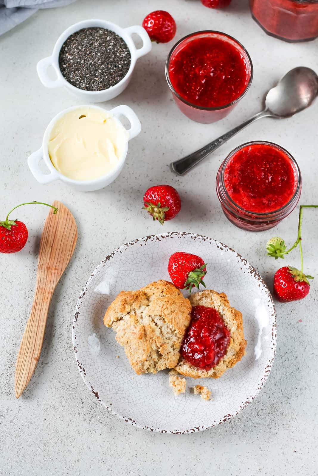 overhead photo of a scone topped with strawberry chia jam and a couple of jars of jam in the background