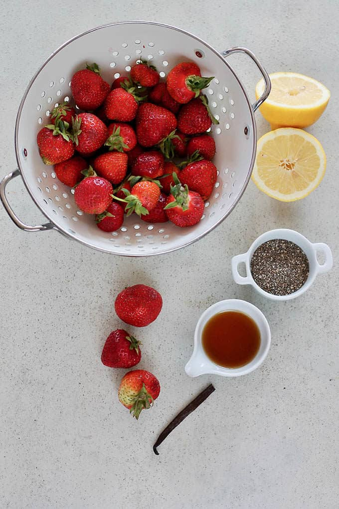 fresh strawberries in a white colander, chia seeds, a cut lemon, maple syrup, and half a vanilla bean on a grey background