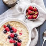 quinoa porridge topped with berries on a dark grey background