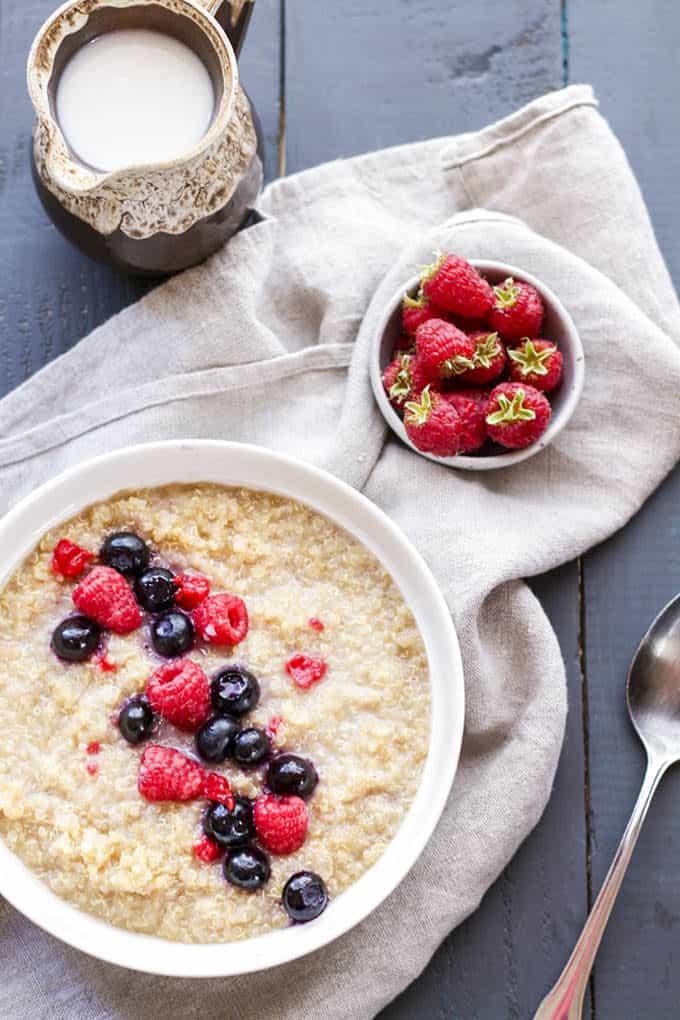 quinoa porridge topped with berries on a dark grey background