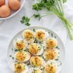 deviled eggs on a white plate sprinkled with herbs