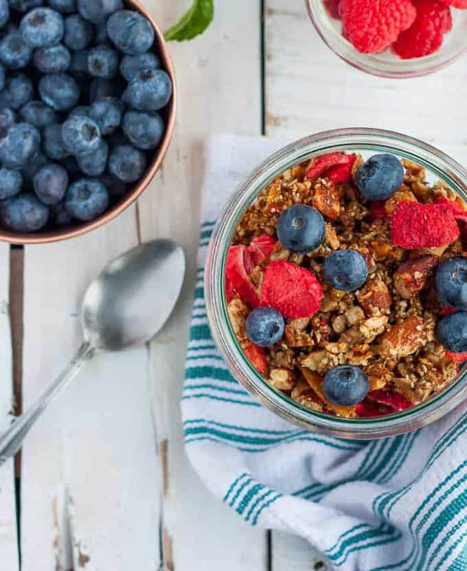 a bowl of paleo muesli topped with berries on a white background
