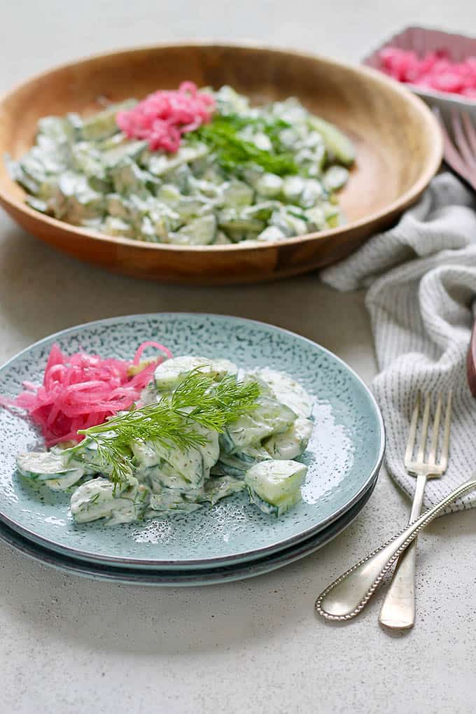 greek cucumber salad on a blue plate with dill and pickled red onions