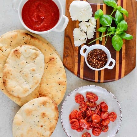 naan bread, semi-dried tomatoes, pizza sauce, mozzarella, basil, and red pepper flakes on a grey background