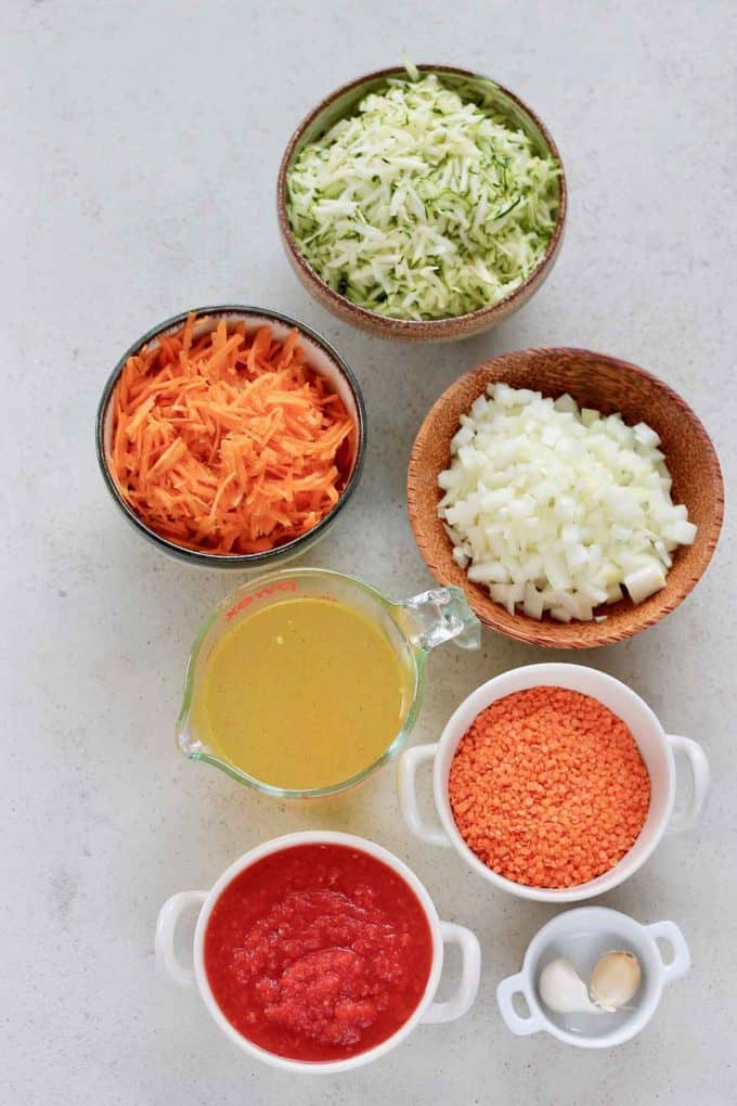 shredded zucchini, shredded carrot, diced onion, garlic, red lentils, crushed tomatoes, and vegetable broth on a grey background