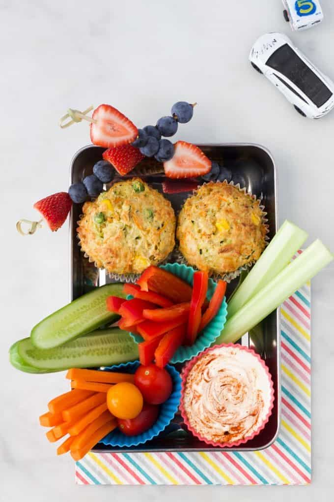 savory muffins in a lunch tray with veggies and dip