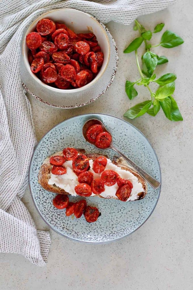 overhead photo of semi dried tomatoes on a piece of toast with ricotta on a blue plate