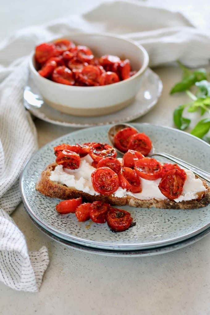A piece of toast on a blue plate topped with ricotta and semi dried tomatoes