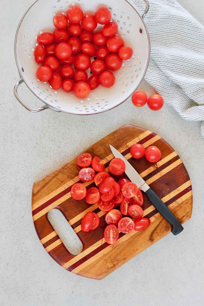 cherry tomatoes in a white colander and a wooden cutting board with sliced tomatoes