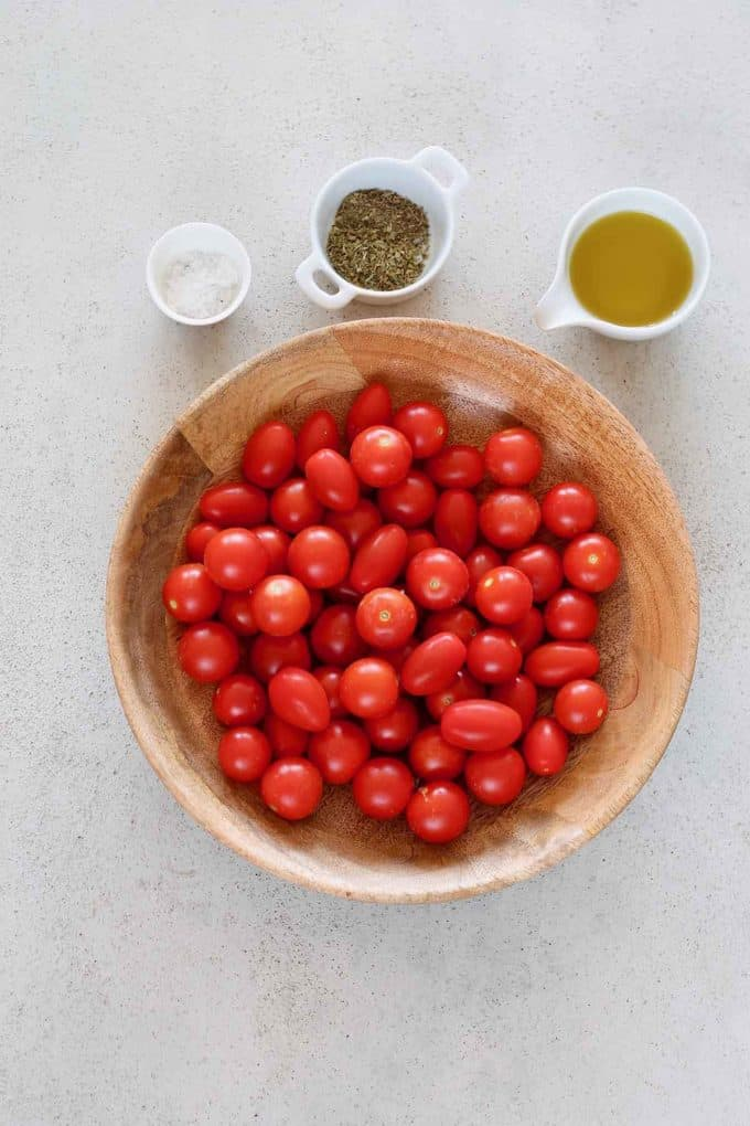 a wooden bowl of cherry tomatoes and small bowls of oil, herbs, and salt to the side