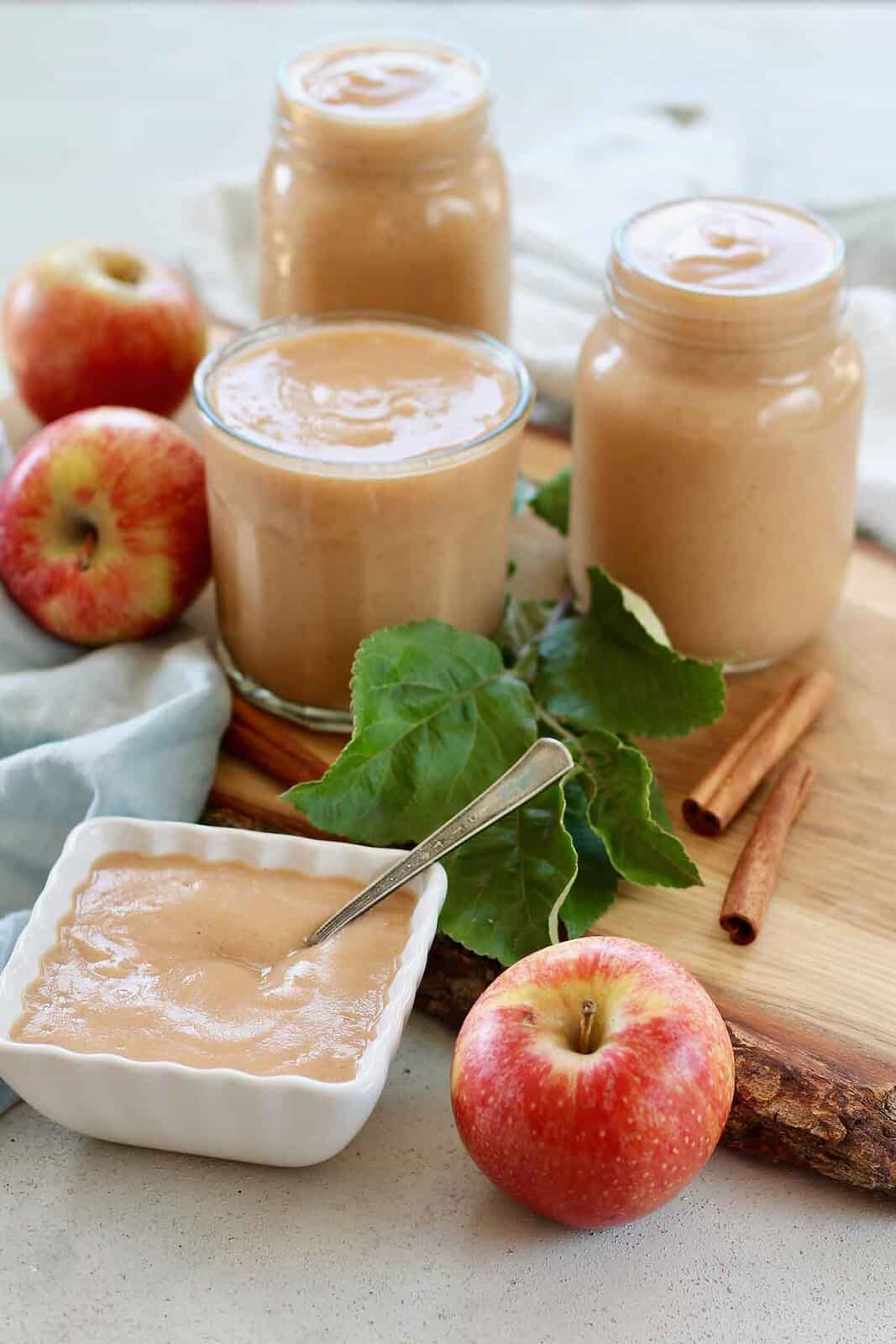 three jars of unsweetened applsauce on a wooden cutting board with apples and leaves