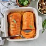 hasselback butternut squash in a white casserole dish