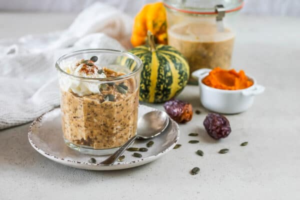 a jar of pumpkin overnight oats on a grey background