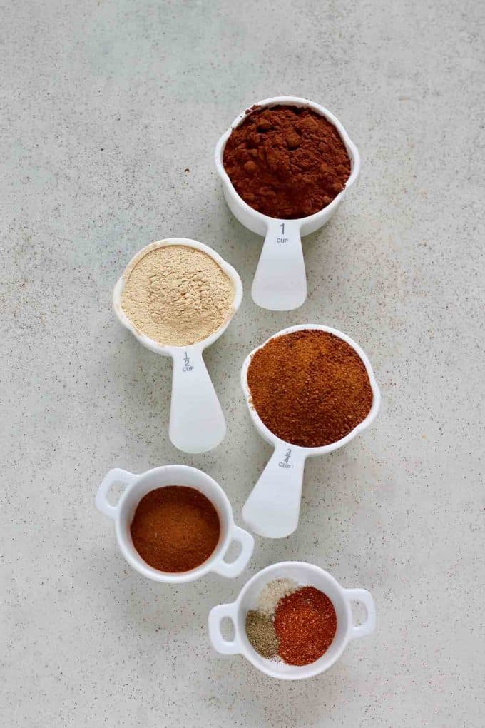 cocoa, maca, coconut sugar, cayenne, cinnamon, black pepper, and salt on a grey background
