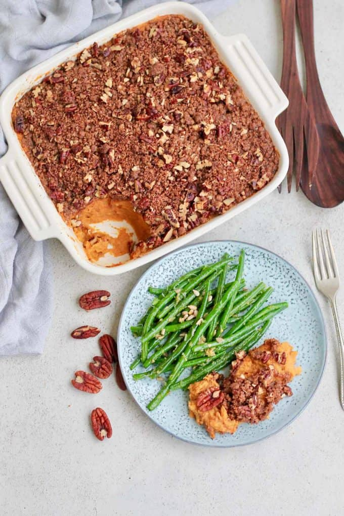 a scoop of vegan sweet potato casserole on a plate with green beans