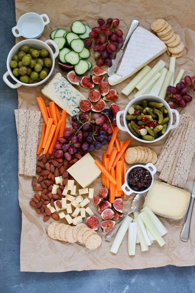 vegetarian cheese board with pickles and olives on a piece of brown paper