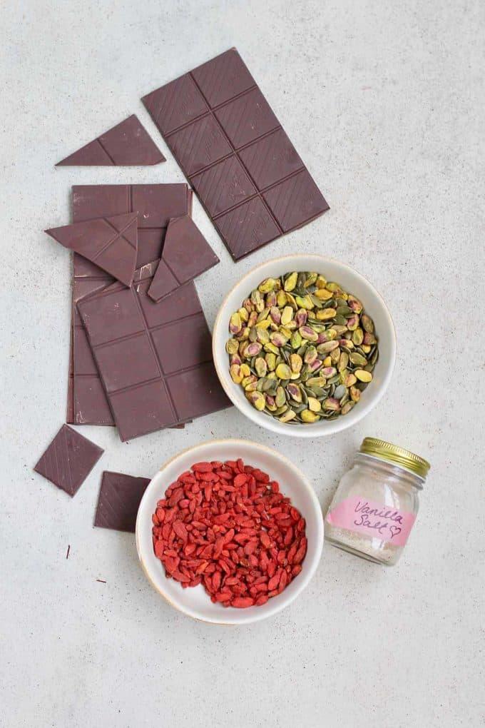 dark chocolate, pistachios, goji berries, and vanilla salt on a grey surface