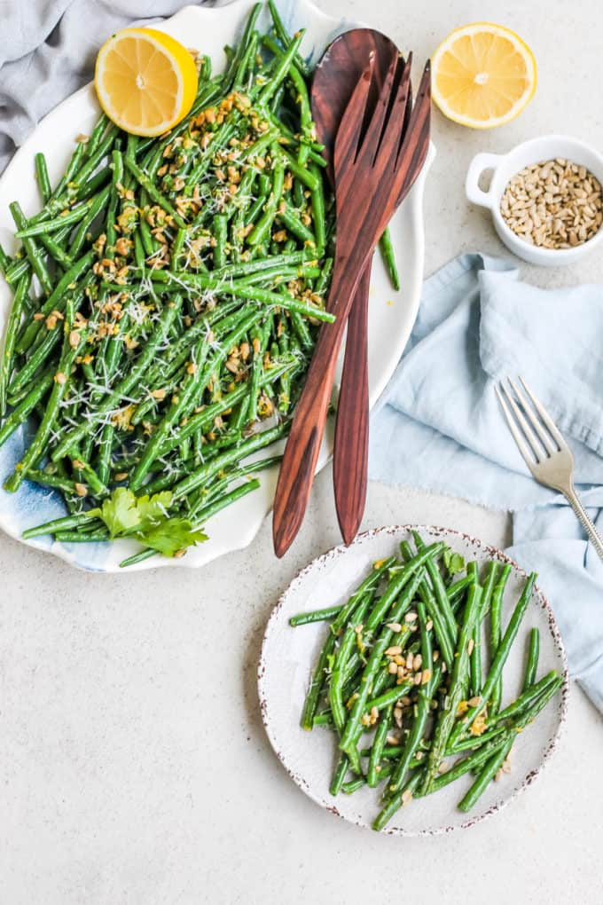 overhead photo of green beans gremolata on a white and blue platter with a small dish of beans to the side
