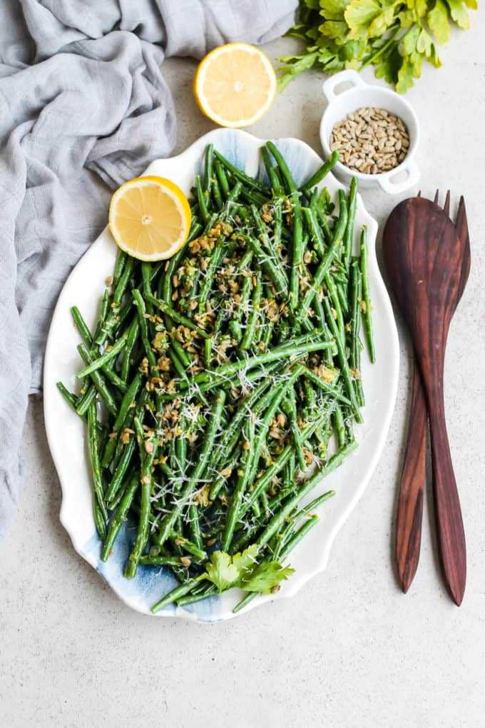 overhead photo of green beans gremolata on a white and blue platter
