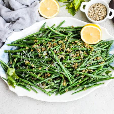 green beans gremolata on a white and blue platter topped with lemon halves