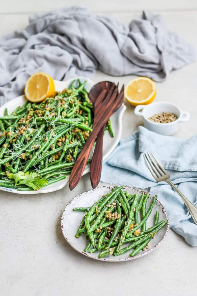 a small white plate with green beans gremolata with a platter of green beans and lemons in the background