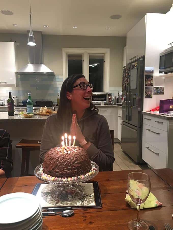 a lady sitting with a chocolate cake in front of her
