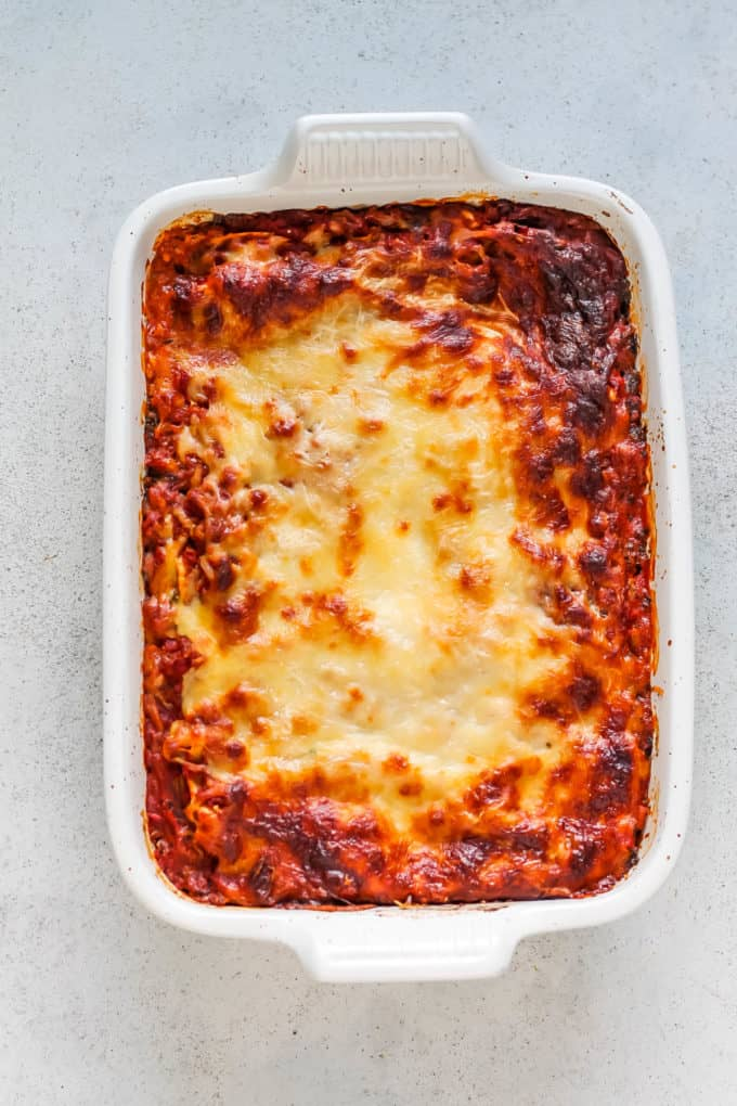 overhead photo of baked kale lasagna in a white casserole dish