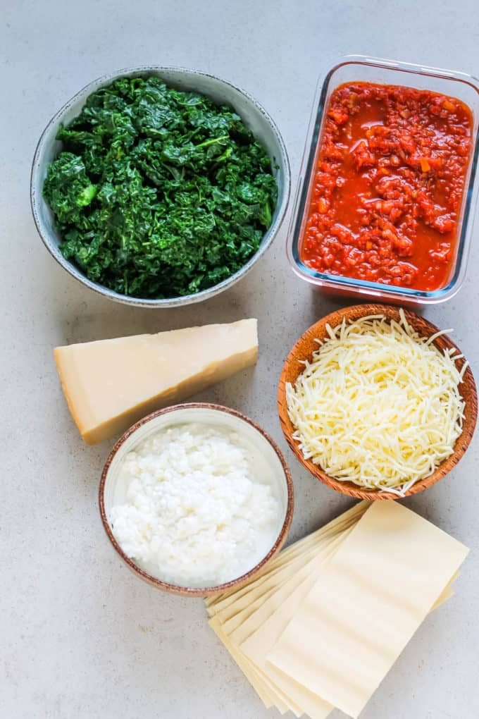 frozen kale, pasta sauce, parmesan, cottage cheese, mozzarella, and lasagna noodles on a grey background
